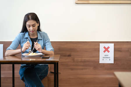 Woman sitting in restaurant eating food and keep distance