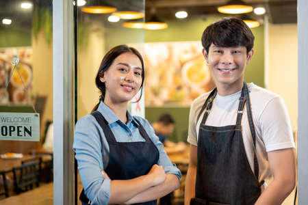 Portrait of Young couple restaurant owner in front of restaurant . waitresses in aprons smiling standing together and looking at camera.