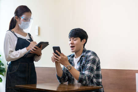 Man order food by smartphone touchless  from waitress with face mask and face shield.