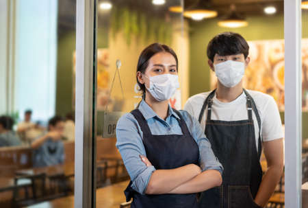 Portrait of Young couple restaurant owner wearing protective mask stand in in front of restaurant .