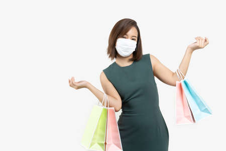 Young Asian woman holding shopping bag wear face mask on white isolate background