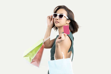 Young Asian woman holding shopping bag and credit card white isolate isolate background .Enjoy Happy Shop Credit Card Payment concept