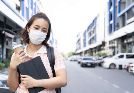 Young student Asian woman wearing face mask to prevent virus
