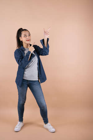 Young happy Asian woman pointing showing hands up presentation to copy space she wearing jean shoot in isolated on pink background