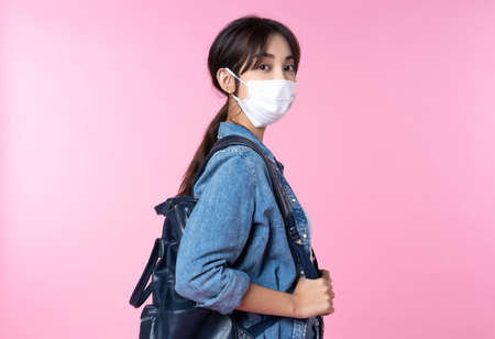 Portrait of young Asian college student wears face mask and backpack isolated over pink background Reklamní fotografie