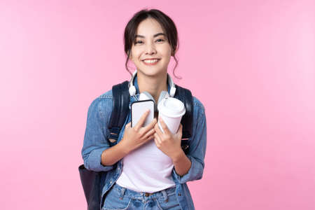 Portrait of young Asian woman student standing with smartphone coffee and backpack.College Teenager University concept.