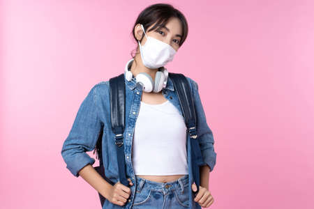 Portrait of young Asian college student wears face mask with headphones and backpack isolated over pink background