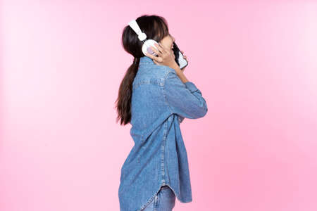 Side view Young Asian woman wearing headphones dancing and listening to music from smartphone shoot in isolated on pink background Reklamní fotografie