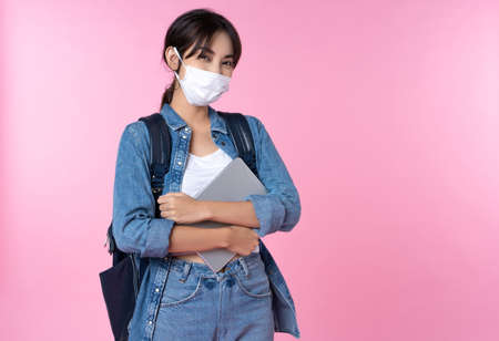 Portrait of young Asian college student wears face mask with laptop and backpack isolated over pink background