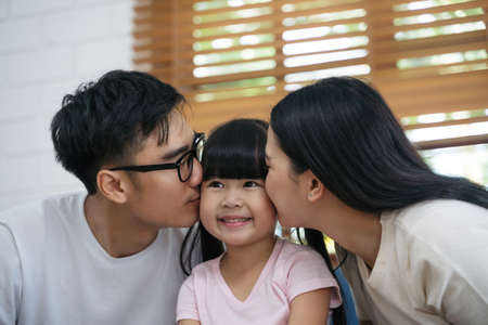 Happy young asian father and mother are kissing her daughter's cheek. Happy family enjoy spending a good time together in a house. Happy asian family.