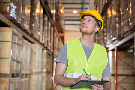 Portrait of young caucasian man checking stock and looking at goods working in a warehouse. A man wearing helmet and reflective jacket working in a warehouse.