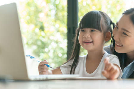 young asian mother on blue shirt enjoy teaching her adorable daughter a homework on a laptop. Asian little girl kind enjoy learning with her beautiful mother.