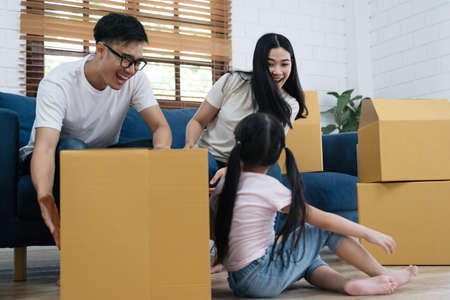 Portrait of happy Asian family moving to new house with cardboard boxes and playing cardboard box