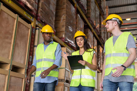 Three male and female warehouse workers are working in a warehouse. African and caucasian warehouse workers are reflective jacket and safety helmet and female worker is holding a check sheet.