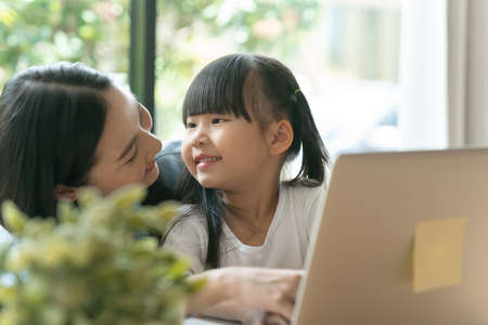 Young asian kid girl smiling at her mother behind a laptop in a house. Happy asian mom and daughter smiling while working from home and girl smiling at her mom.