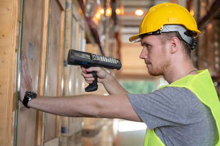 Young man scanning a barcode working in a warehouse. Young caucasian handsome man wearing helmet and reflective jacket working in a warehouse. Stock fotó