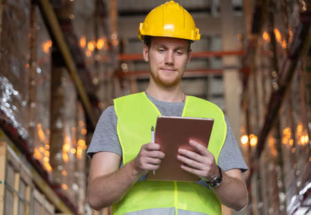 Man looking at check sheet to checking inventory by lablet. A young caucasian man wearing helmet and reflective jacket working in a warehouse.