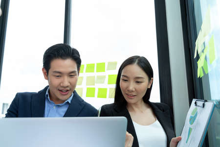 Asian business man and woman are discussing and talking in front of a laptop. Two young worker wearing a suit looking at a laptop.