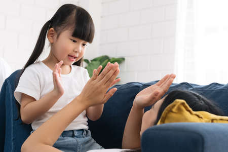 Asian cute girl enjoy playing with her mom on blue sofa. mother is playing wiith her daughter on sofa. Happy asian mom and daughter spending a good time togather. Reklamní fotografie