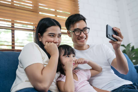 Family smiling at camera. Happy family taking a selfie, smiling at a phone at home.
