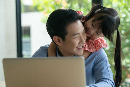 Asian father on blue shirt working from home with his little cute girl daughter. Asian kid hug his dad from behind while her father is working on a laptop. Reklamní fotografie
