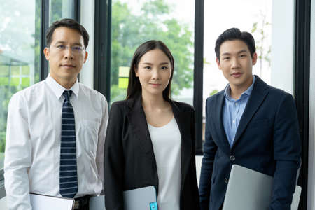 Portrait of three asian business men and woman are standing with a confidence. A teamwork businessman who standing at the office. Asian professional business people are standing with friendly face.