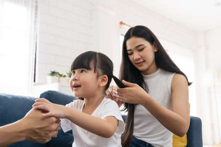 Beautiful Asian young mother is making hairstyle to her cute daughter. Happy family enjoy spending a good time togather. Asian little girl kid enjoy playing with her parents. Reklamní fotografie