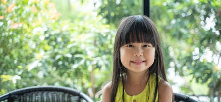 Smiling asian girl sitting on a chair looking at a camera with green background behind. Portrait adorable asian girl with smiling happy face. Reklamní fotografie - 162292068