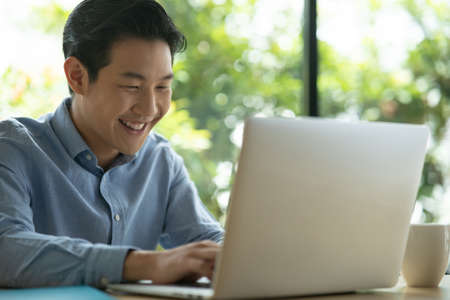 Asian man on blue shirt smiling while using a laptop. Happy face smiling asian black short hair man looking at a laptop with green background. Freelancer working and looking at laptop. Reklamní fotografie