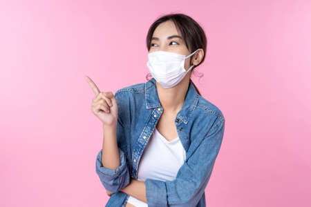 Young happy Asian woman pointing finger hands up to copy space wearing hygienic mask