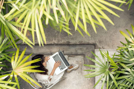 Top view woman using laptop with nature tree park.