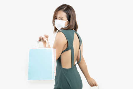 Young Asian woman holding shopping bag wear face mask