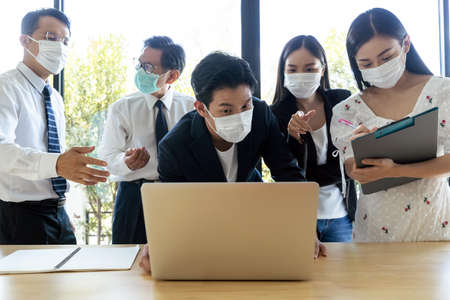Group of Asian business people meeting and working in office and wear mask