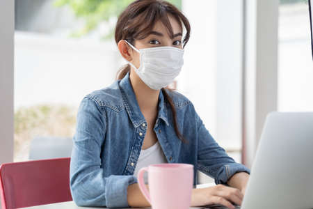 Young Asian student girl working at a coffee shop looking at camera with a laptop she wearing hygienic mask Stok Fotoğraf