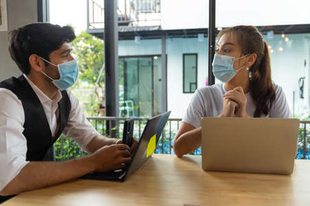 Two Asian people wearing mask meeting working with laptop at coffee shop