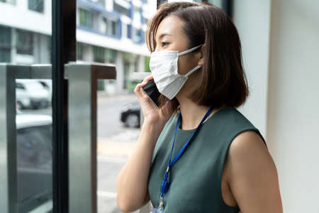 Portrait Asian business woman wearing hygienic mask talking on the phone outside office.