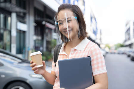 Young student Asian woman holding coffee and tablet wearing face shield to prevent virus