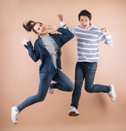 cheerful positive Asian couple  jumping in the air