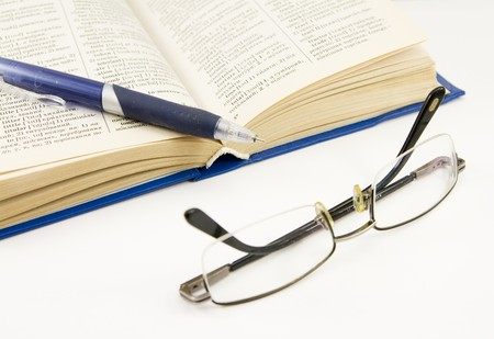 book, pen and glasses isolated on white photo
