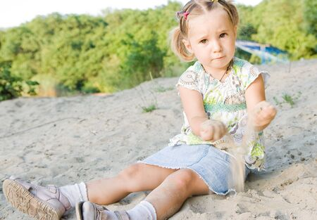 girl playing with sand photo