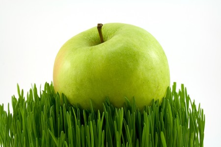 nutricion: green apple on green grass isolated on white