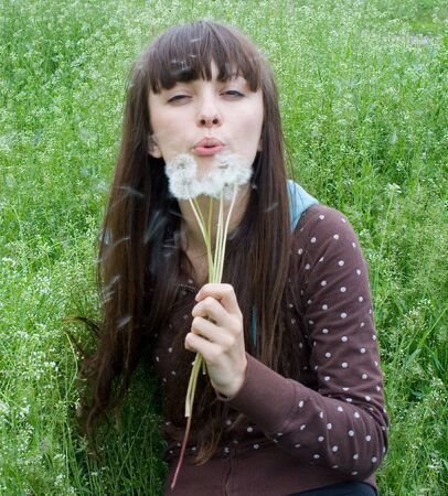 young girl blows a dandelion photo
