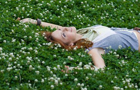 lying in grass: chica en la hierba verde Foto de archivo