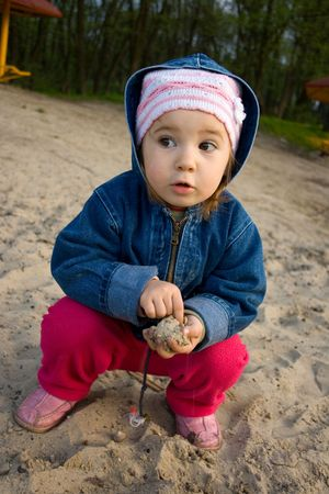 a faction: little girl playing in sand on river back Stock Photo