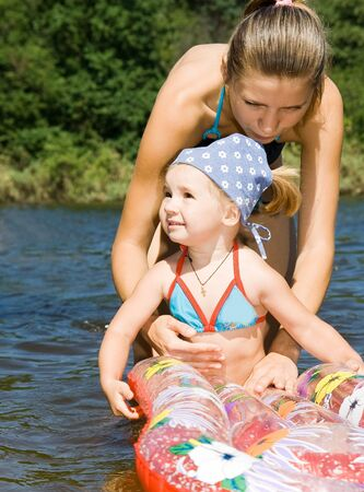 little girl with mother in river photo