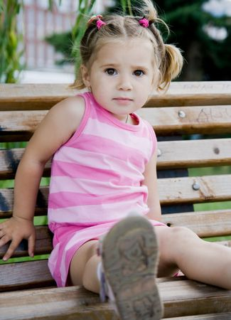 little girl sitting: little girl on the bench