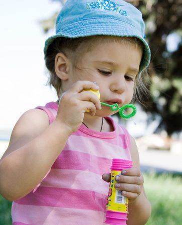 little girl blowing bubbles photo