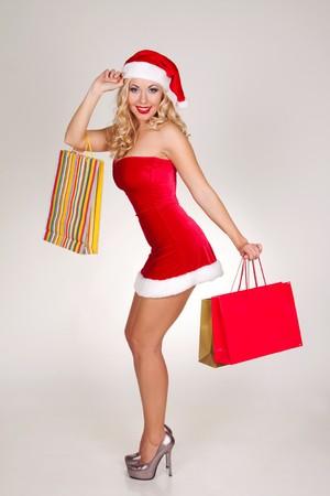 買い物袋のクリスマスの衣装で美しいブロンドの女の子
