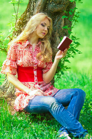 portrait of young woman with book outdoor photo