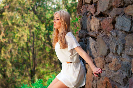 portrait of blond woman in white dress outdoor photo